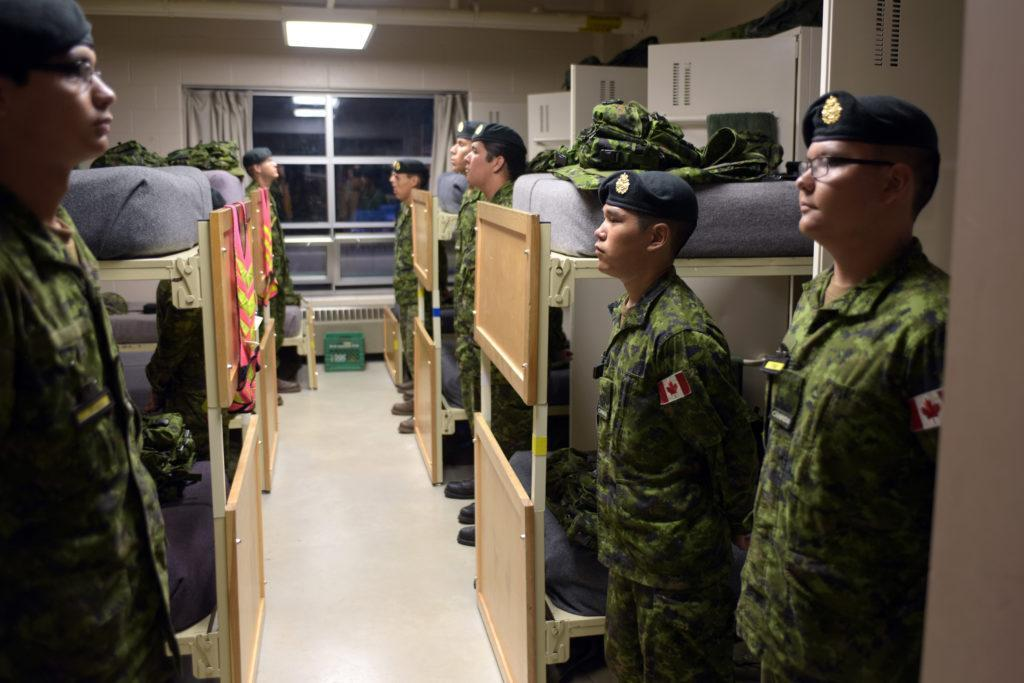 Black Bear Aboriginal Program 2015 Members of the Black Bear Program 2015, stand by their beds waiting for a night inspection by the course instructior in prepeation to prepare for a morning inspection of their bed spaces by the course Officer in Command at 5 Canadian Division Support Base Gagetown on the evening of 4 Aug 2015. Black Bear is a six-week training and leadership program that fosters the relationship between CanadaÕs Aboriginal communities and the Canadian Armed Forces.  Photo: WO Jerry Kean, 5 Cdn Div Public Affairs LH01-2015-018-006