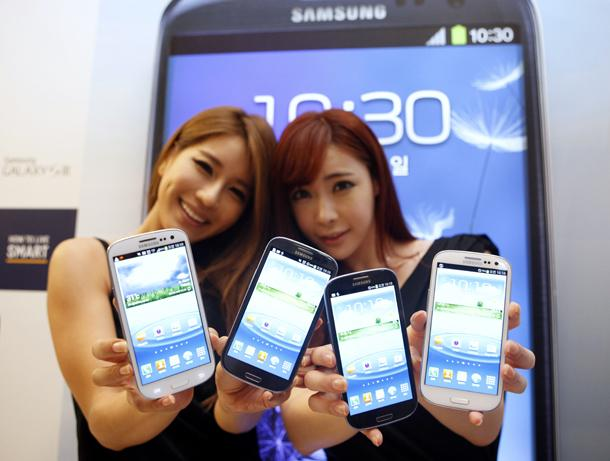 Models hold new Galaxy S III devices as they pose for photographers during an event to launch the smartphone in the local market at the headquarters of Samsung Electronics in Seoul June 25, 2012. Samsung Electronics expects sales of its new Galaxy S III, launched at the end of last month as a main rival to Apple's iPhone, to top 10 million during July, making it the South Korean group's fastest selling smartphone. REUTERS/Lee Jae-Won (SOUTH KOREA - Tags: BUSINESS TELECOMS SCIENCE TECHNOLOGY)